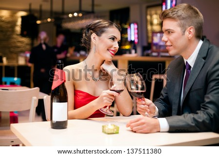 happy affectionate couple clinking glasses at restaurant toasting and looking at each other - stock photo