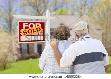 Happy Affectionate Senior Couple Hugging in Front of Sold Real Estate Sign and House. - stock photo
