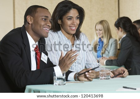 Happy African American business people communicating with colleagues in the background - stock photo