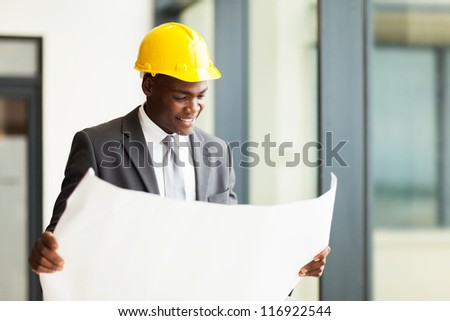 happy african american businessman looking at blueprint