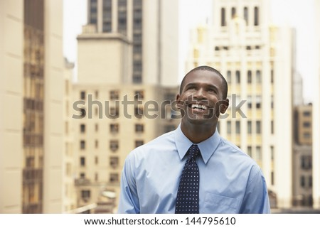 Happy African American businessman looking up against office buildings - stock photo