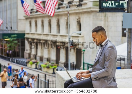 Happy African American Businessman traveling, working in New York. Wearing gray blazer, bow tie, college student siting on Wall Street, reading, working on laptop computer. Instagram filtered effect.  - stock photo