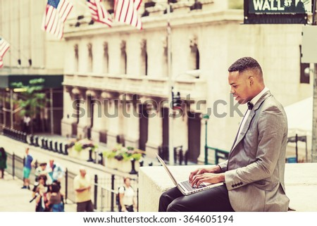 Happy African American Businessman traveling, working in New York. Wearing gray blazer, bow tie, college student siting on Wall Street, reading, working on laptop computer. Retro filtered effect.  - stock photo