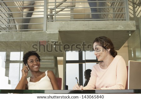 Happy African American businesswoman using mobile phone with female colleague in conference room - stock photo