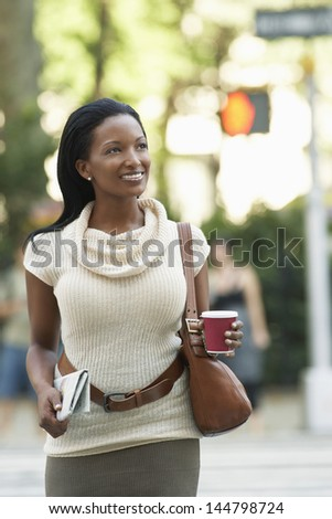 Happy African American businesswoman with newspaper and coffee cup walking on street - stock photo