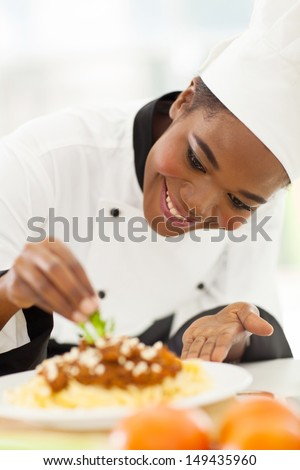 happy african american chef in kitchen decorating pasta dish - stock photo