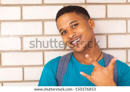 happy african American college boy giving hand sign