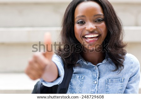 happy african american college girl with thumb up - stock photo