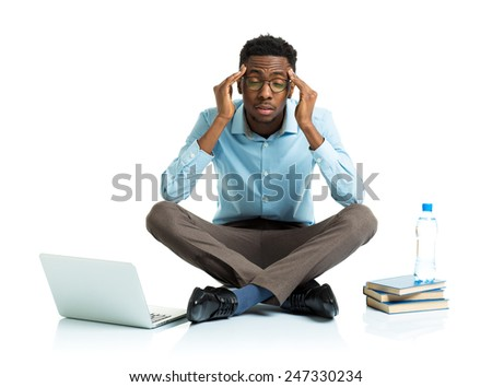 Happy african american college student in stress sitting with laptop, books and bottle of water on white background - stock photo