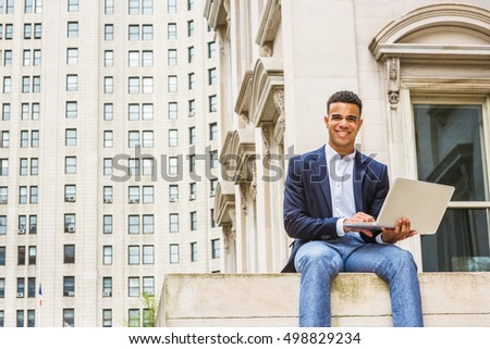 Happy African American college student studies in New York. Wearing blue blazer, white shirt, young black man sits on street outside vintage office building on campus, works on laptop computer, smiles