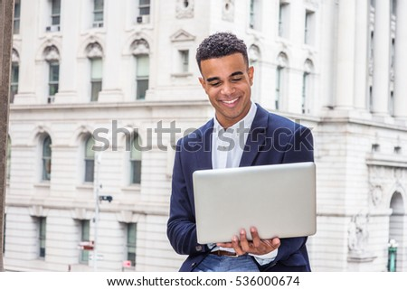 Happy African American college student studying in New York, wearing black blazer, sitting by vintage office building on campus, reading, working on laptop computer, smiling. Color filtered effect