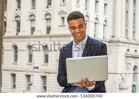 Happy African American college student studying in New York, wearing black blazer, sitting by vintage office building on campus, reading, working on laptop computer, smiling.