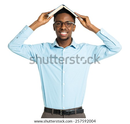 Happy african american college student with book on his head standing on white background - stock photo