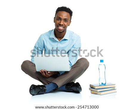 Happy african american college student with laptop and some books sitting on white background - stock photo