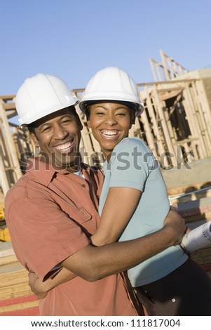 Happy African American couple at construction site