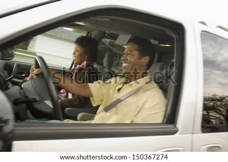 Happy African American couple driving car