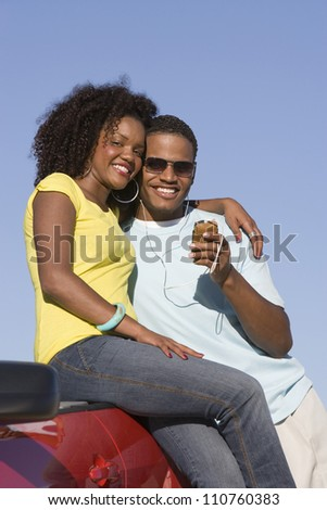 Happy African American couple listening music near car