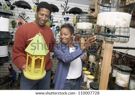 Happy African American couple selecting birdhouse in shop - stock photo