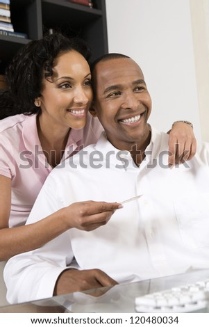 Happy African American couple shopping with credit card and computer - stock photo