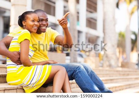 happy african american couple sitting outdoors in the city - stock photo