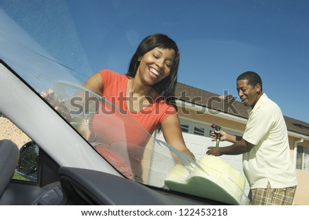 Happy African American couple washing car together - stock photo