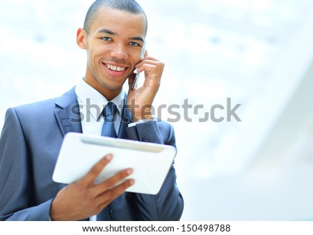 happy african american entrepreneur using tablet computer and talking on phone - stock photo