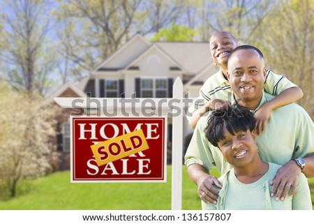 Happy African American Family In Front of Sold Real Estate Sign and House.