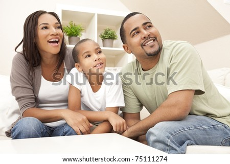 Happy African American family, parents and son, sitting on a sofa at home laughing and smiling - stock photo