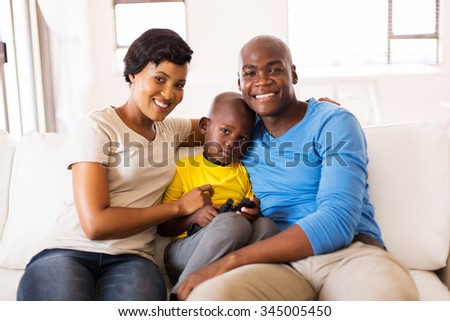 happy african american family sitting on the couch at home - stock photo