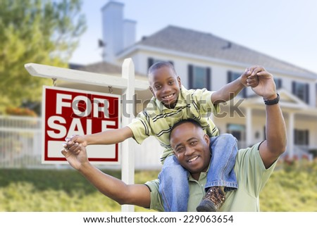 Happy African American Father and Son in Front of Home and For Sale Real Estate Sign.