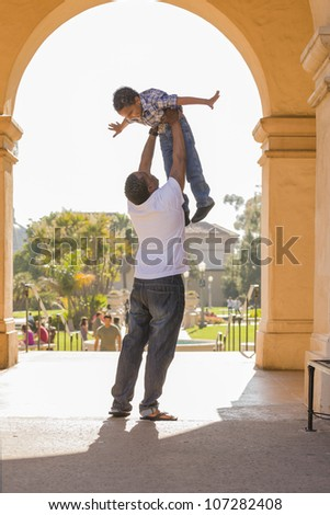 Happy African American Father Lifts Mixed Race Son Over His Head in the Park. - stock photo