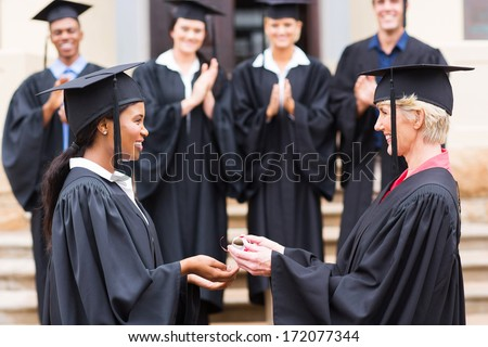 happy african american female graduate receiving diploma from dean - stock photo