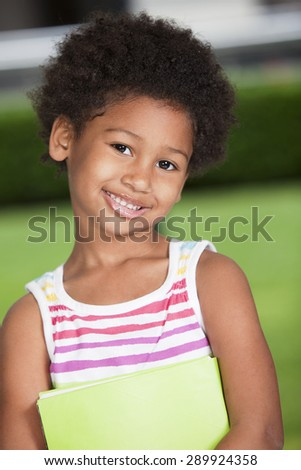Happy african american girl with book - stock photo