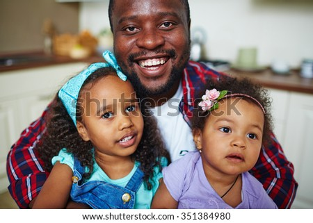 Happy African-American man and his two cute daughters - stock photo