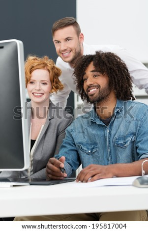 Happy African American man at work smiling as he sits with his colleagues in the studio at a computer creating a new innovation or design - stock photo