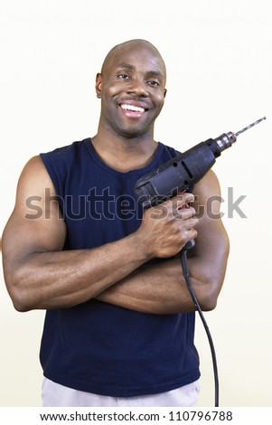 Happy African American man holding drill - stock photo