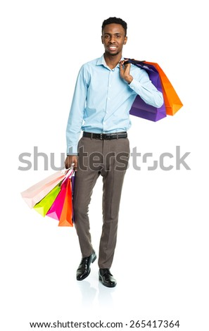 Happy african american man holding shopping bags on white background. Holidays concept - stock photo
