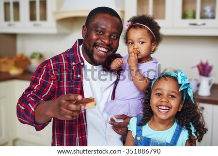 Happy African-American man with adorable daughters looking at camera
