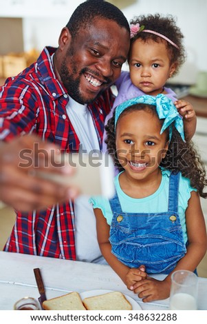 Happy African-American man with two adorable daughters making selfie during breakfast