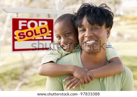 Happy African American Mother and Child In Front of Sold Real Estate Sign. - stock photo