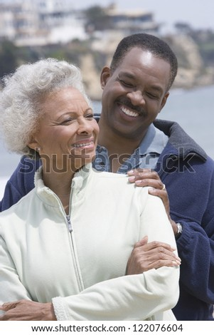 Happy African American mother and  son standing together