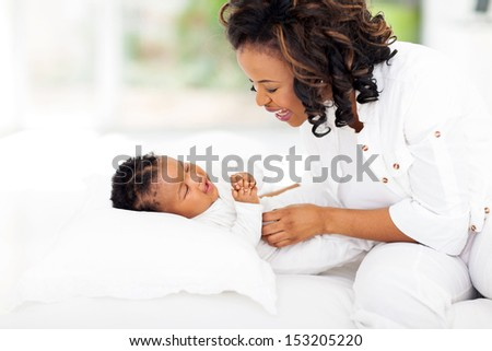 happy african american mother playing with her little daughter on bed - stock photo
