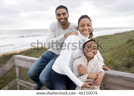 Happy African-American parents with ten year old boy smiling and hugging at beach