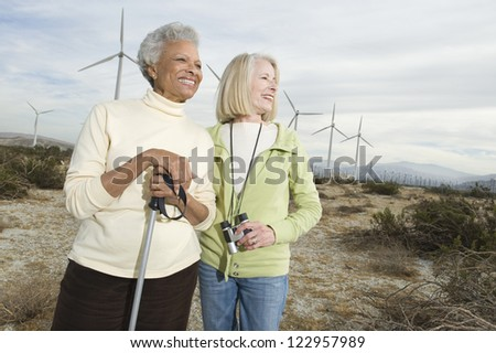 Happy African American senior woman holding trekking pole enjoying vacation with friend at wind farm