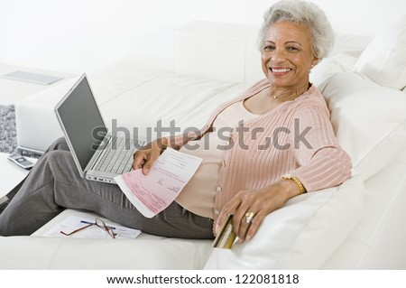 Happy African American senior woman making online payment of bills using laptop - stock photo