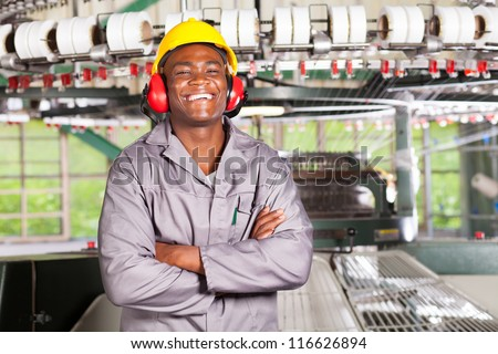 happy african american textile worker portrait in front of machinery