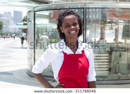 Happy african american waitress in front of the restaurant - stock photo