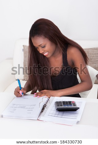Happy African American woman calculating finance at home