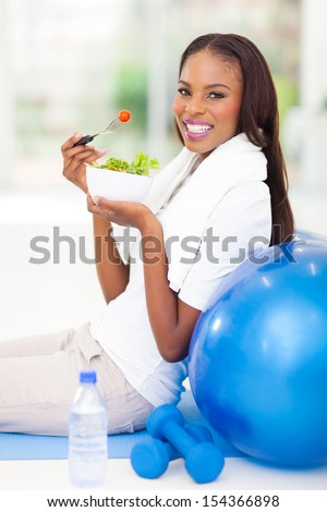 happy african american woman having green salad after working out - stock photo