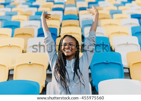 Happy african american woman standing in amongst the rows of empty seats at stadium cheering with her arms raised punching air - stock photo